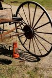 Lantern hanging from a axle of an old horse pulled buggy. A red lantern hangs from the wooden axle holding a large buggy wheel with wooden spokes Stock Photos