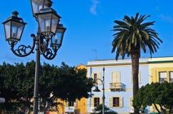 Lantern if front of colorful buildings at Carloforte harbor, San Pietro island, Sardinia Royalty Free Stock Photos