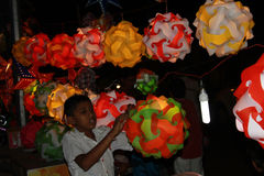 Lantern Kid. A small boy from India adjusts the lanters in his streetside shop before Diwali festival starts in India Royalty Free Stock Images
