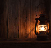Lantern lamp light dark wooden wall table Stock Images