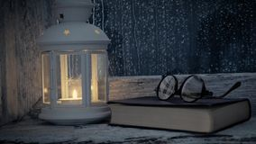 Lantern lit, book and glasses on the sill of an old window, it rains outside stock footage