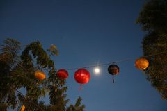 Lantern in the night skyat Hoi An lantern festival in November 2018. Moon lining up with line of lanterns stock image
