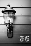 Lantern at number 35. Black and white image of a lantern next to the door of number 35 Stock Photo