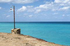 Lantern at the ocean. A symbolic place to meet in the evening, a lantern standing on the coastline of Cuba, Varadero, near the azure waters of the Atlantic ocean Stock Photography