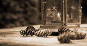 Lantern. Old lantern and pine cones on a wooden table in sepia Royalty Free Stock Photos