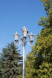 Lantern in the park. In sunny day on a background of the green trees and sky Royalty Free Stock Photo
