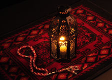 A lantern and rosary. Arabic lantern on red carpet with wooden rosary Royalty Free Stock Photos