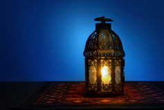 A lantern and rosary. An illuminated Arabic lantern on blue background
