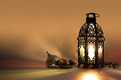 Lantern, rosary beads and date fruits with color reflection on background. stock photos