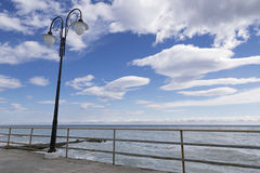 Lantern on the seafront against the sky with clouds Royalty Free Stock Images