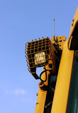Lantern, secure grille, on the roof of a bulldozer at  construction site against the blue sky Stock Photos