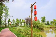 Lantern-shaped streetlamp by lakeside red path in sunny spring Stock Photography