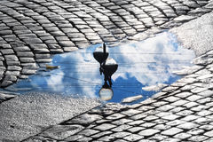 Lantern and sky reflection in  puddle Stock Photo