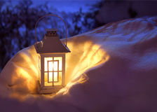 Lantern in snow. White Christmas lantern in snow, with yellow candle light, on mysterious dark blue background stock photography