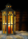 Lantern in the snow, wood background Stock Photo