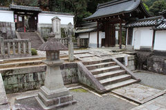 A lantern and stone steles decorate the courtyard of a temple (Japan) Stock Photos