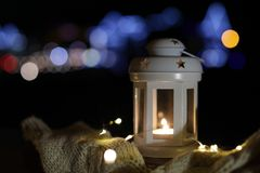 Lantern, sweater and Christmas lights outdoors on winter night. Space for text royalty free stock photos