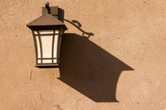 Lantern on a wall. An old-fashioned lantern on a textured wall Royalty Free Stock Image