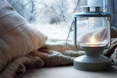 Lantern on windowsill. Lantern and pillows on windowsill with winter view royalty free stock image