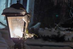 Lanterna com neve e um ramo de uma luz amarela de incandescência de árvore de Natal Neve na lanterna, noite do inverno no parque imagem de stock