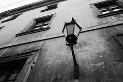 Lanterna d'annata della via nel retro stile sulla parete stagionata di vecchia casa storica in bianco e nero Immagine Stock