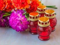 Lanterna da memória com velas e ramo de flores artificiais sobre Foto de Stock