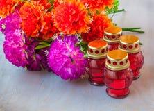 Lanterna da memória com velas e ramo de flores artificiais sobre Fotos de Stock