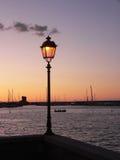 Lanterna de incandescência da rua no porto, no por do sol Imagens de Stock