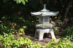 A lanterna de pedra na sombra entre a vegetação rasteira sempre-verde planta o pa Imagem de Stock Royalty Free