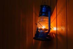 Lanterna de querosene velha que pendura na parede de madeira amarela Foto de Stock Royalty Free