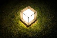 Lanterna del cubo di illuminazione su erba alla notte. Fotografia Stock