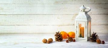 Lanterna della luce della candela con le pigne, i dadi ed i mandarini come chr immagine stock