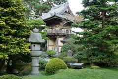 Lanterna di pietra tramite l'entrata giapponese del giardino Fotografie Stock