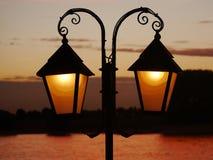 A lanterna do ferro forjado iluminou, como uma silhueta na frente do céu iluminado pelo por do sol no fundo borrado imagem de stock royalty free