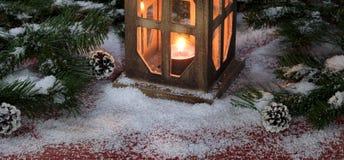 Lanterna do vintage com vela ardente em b de madeira vermelho rústico nevado Imagem de Stock