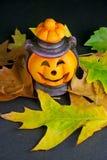 Lanterna e fogli di Halloween su priorità bassa nera Immagine Stock