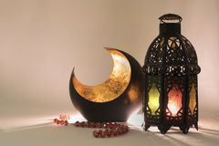Lanterna e rosário em um pano do cetim com efeito do fulgor atrás da cena Imagens de Stock
