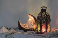 Lanterna e uma forma crescente de cobre em um pano do cetim Fotos de Stock