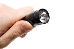 Lanterna elétrica preta em uma mão isolada. Imagem de Stock