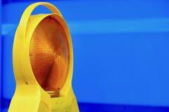 Lanterna gialla della costruzione di strade contro il contenitore blu Fotografia Stock