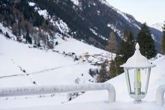 Lanterna innevata fra due inferriate con la stazione sciistica delle alpi del Tirolo su fondo Fotografie Stock