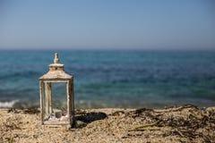 Lanterna rústica com vela e conchas do mar pelo beira-mar fotografia de stock