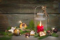 Lanterna rústica do Natal com luz de vela e fundo de madeira Imagens de Stock