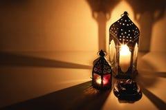 Lanternas árabes decorativas, velas ardentes que incandescem na noite Placa com fruto da data na tabela Festivo dourado foto de stock royalty free