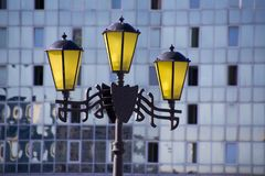 Lanternas amarelas estilizados do vintage no fundo de uma construção de vidro moderna Imagens de Stock