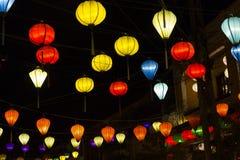 Lanternas coloridos iluminadas amarradas através da rua fotografia de stock royalty free