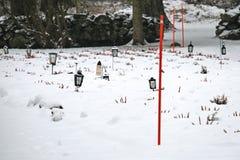 Lanternas com velas na jarda grave do cemitério coberta com a neve no inverno imagem de stock royalty free