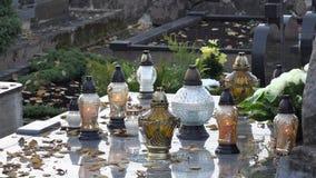 Lanternas da vela e folhas de outono na pedra grave do túmulo no cemitério closeup 4K vídeos de arquivo