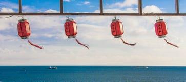 Lanternas de papel chinesas vermelhas contra um céu azul e um mar Imagem de Stock Royalty Free