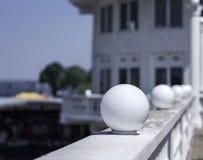 Lanternas redondas brancas em um fundo natural borrado Um close-up de luzes de rua de vidro brancas esféricas do plafond Foto de Stock Royalty Free